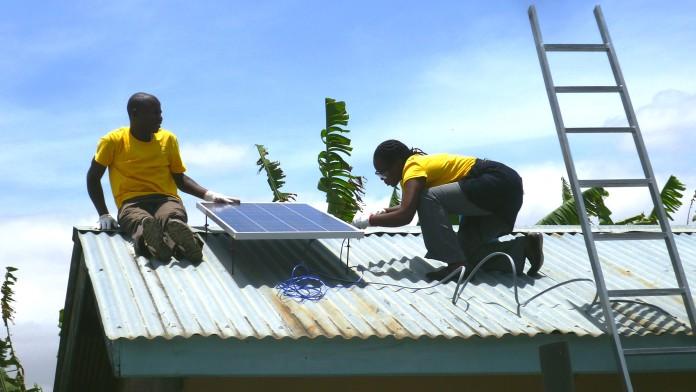 Techniker in Afrika installieren eine Solaranlage auf einem Hausdach