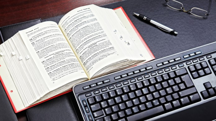Tastatur und Gesetzestext liegen auf einem Tisch