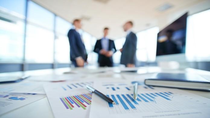 Auf einem Tisch liegen Dokumente, im Hintergrund besprechen sich drei Geschäftsmänner