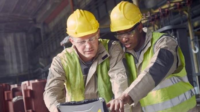 Zwei Männer schauen auf einen Laptop in einer Werkstatt.