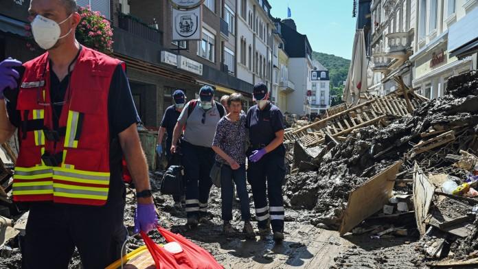 Helfende der Johanniter in Bad Neuenahr-Ahrweiler begleiten eine Seniorin aus ihrer Wohnung.