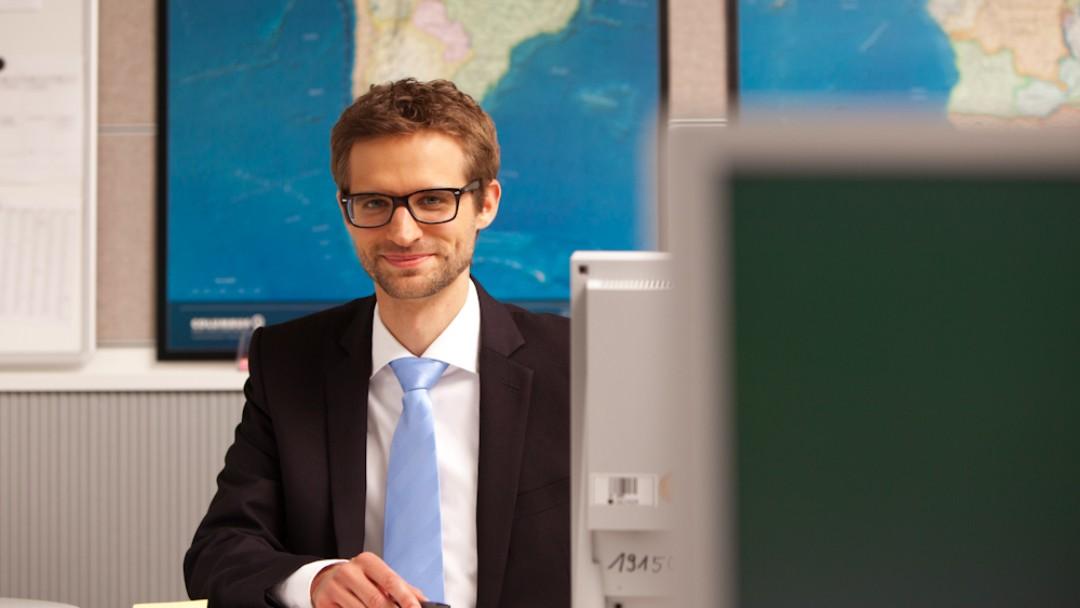 Mitarbeiter vor einer Weltkarte an einem Schreibtisch