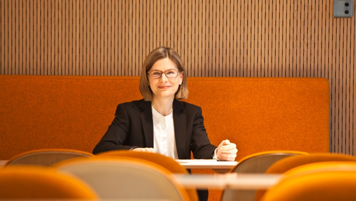 Eine Geschäftsfrau vor einem orangefarbigen Hintergrund