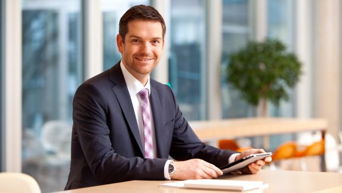 Ein Geschäftsmann an einem Stehtisch mit einem Tablet-PC in der Hand