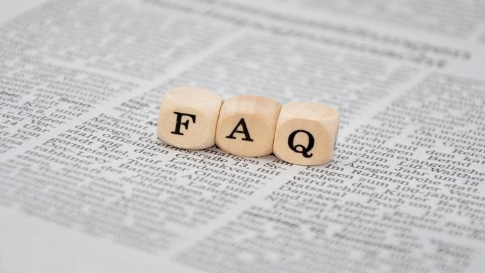 FAQ-Schriftzug aus Holzwürfeln auf einer Zeitung