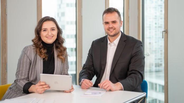 eine junge Mitarbeiterin und ihr Kollege an einem Besprechungstisch