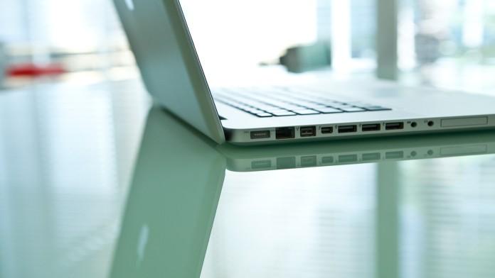 Aufgeklappter Laptop auf einem verspiegelten Schreibtisch