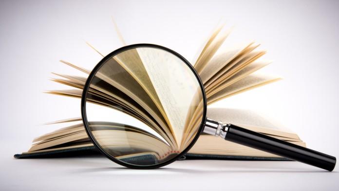 Eine Lupe vor einem Buch