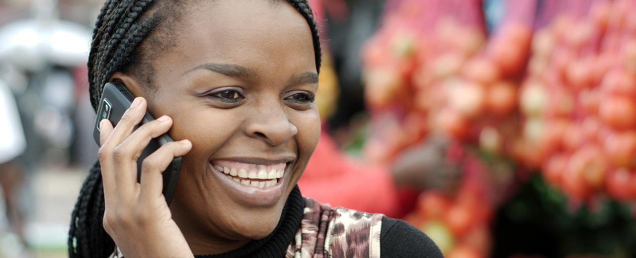 Eine afrikanische Frau telefoniert mit einem Smartphone, hinter hier ein Marktstand mit Gemüse