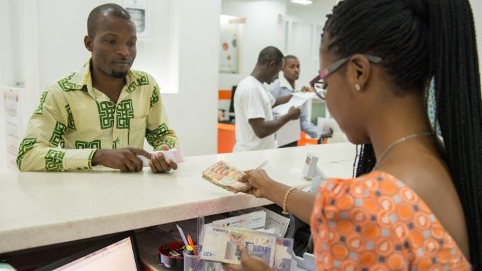 Eine Bankmitarbeiterin zahlt einem Kunden Geld aus.
