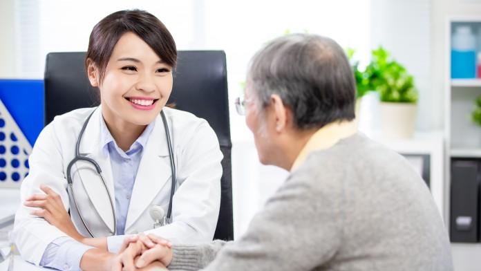 Behandlung eines älteren Patienten durch junge Ärztin.