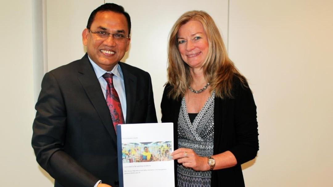 Ein Geschäftsmann aus Bangladesch und eine europäische Geschäftsfrau halten eine Studie in den Händen.