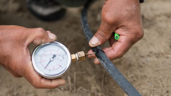 Ressourcen schonen - ein Mitarbeiter misst den Wasserdruck bei einem Bewässerungsschlau.